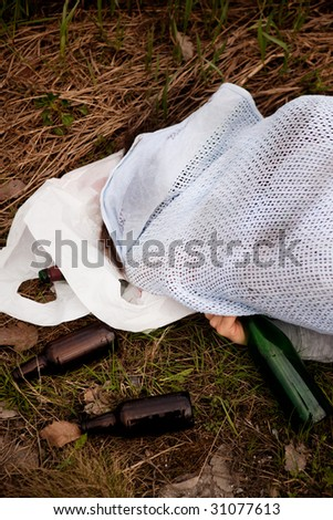 An alcoholic laying in the ditch with liquer bottles - stock photo