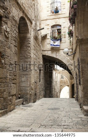 An alley in the Jewish quarter of the old city of Jerusalem, Israel. Hanging from the bottom window is an Israel flag with the symbol of Jerusalem instead of the star of David. - stock photo