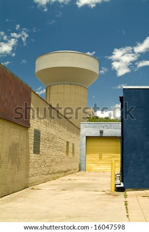 An alley with a view of a large water tower and colorful garage door.