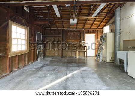 An almost empty wooden garage to be used as storage for junk that will be collected over the years. - stock photo