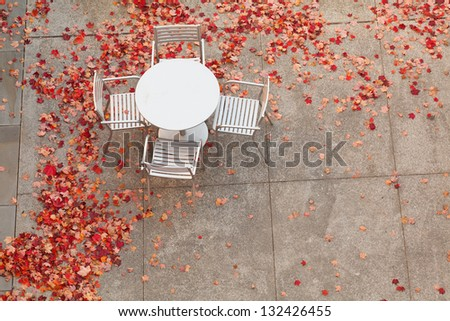 An aluminum table with four chairs surrounded by fallen red maple leaves. - stock photo