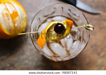 An Amarena cherry garnishes an Old Fashioned cocktail. - stock photo