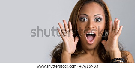 An amazed and shocked woman isolated over a silver background.  Lots of copy space for your text. - stock photo