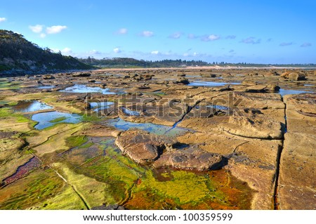 An amazing platform of colorful  rocks is revealed as the tide retreats at Bateau Bay, NSW, Australia - stock photo