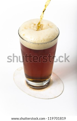 An amber ale being poured into a pint glass on a coaster with a plain white background. - stock photo
