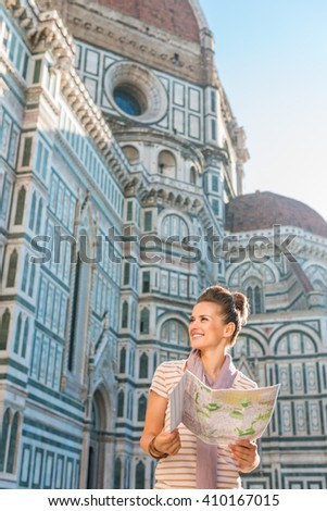 An amble around awe-inspiring Duomo in Florence, Italy. Happy woman tourist with map looking on something while standing in the front of Duomo - stock photo