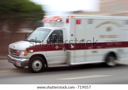 An ambulance blazes by, it's sirens whaling.  An intentional camera blur gives a feeling of a rushed tension to the scene. - stock photo