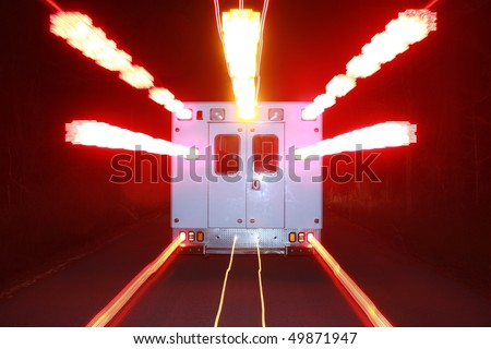 an ambulance speeds toward an emergency with its warning lights flashing - stock photo