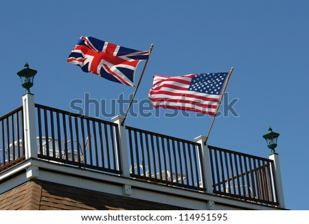 An American and British flag waving in the wind on a rooftop deck - stock photo