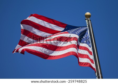 An American flag blowing proudly in the wind. - stock photo