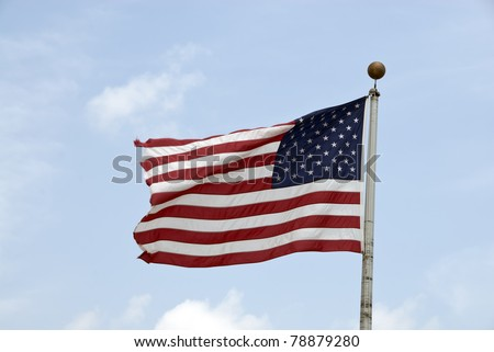 an american flag flying high with the wind - stock photo