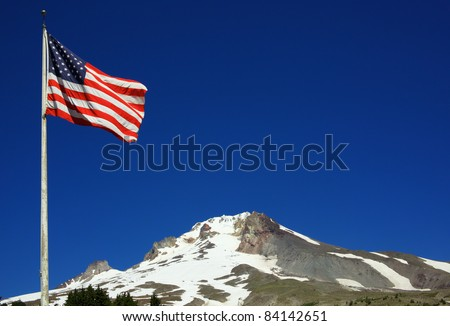 An American Flag flying with Mount Hood in the background with a deep blue sky - stock photo