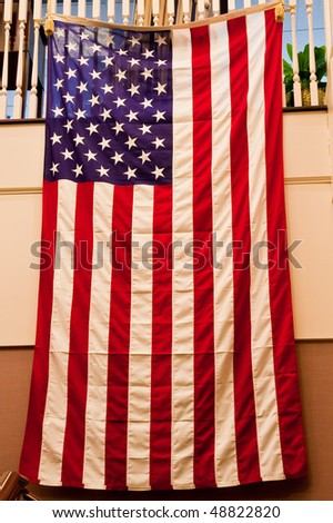 An American flag hanging on a staircase banister - stock photo