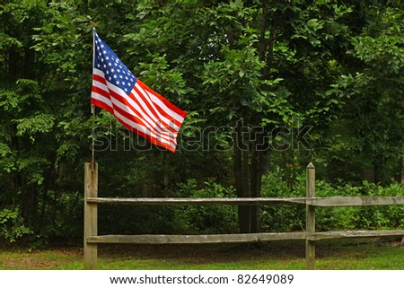 An American flag on a fence post blowing in the wind on a summer day with room for your text - stock photo