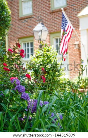 An American flag on a nice brick house with a lush spring garden in front - stock photo