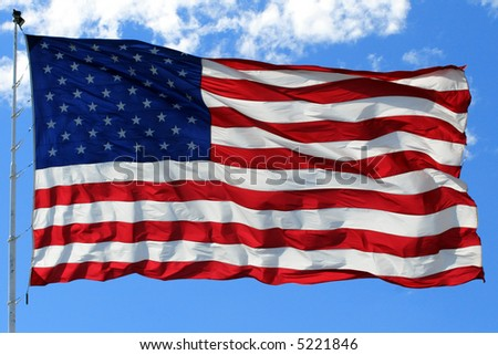 An American flag waves in the breeze, with blue sky in the background.