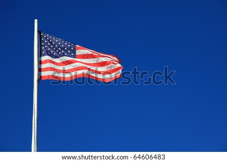 An American flag waving against a blue sky in the breeze - stock photo