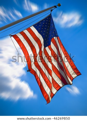 An american flag waving over a blue sky. Zooming effect.
