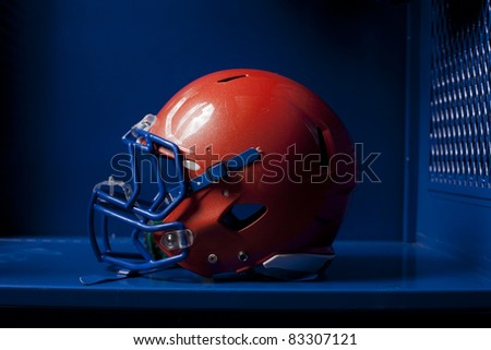 An american football helmet sits in an empty locker. Dramatic lighting. - stock photo