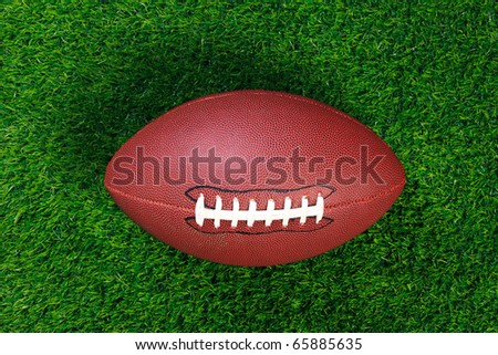 An American football on grass - stock photo
