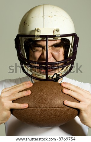 An American football player. Headshot through facemask with ball.