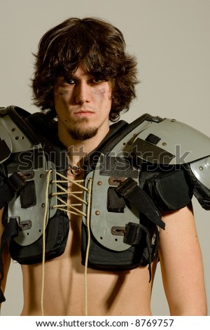 An American football player. Shirtless with shoulder pads. - stock photo