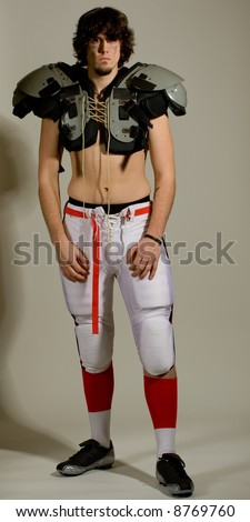 An American football player. Shirtless with shoulder pads.