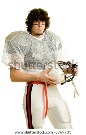 An American football player. Standing with helmet.