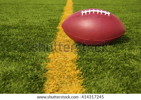 An American football resting just over the goal line for a touchdown - stock photo