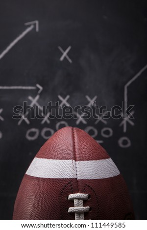 An American football with a play drawn up on a chalkboard in the background. - stock photo