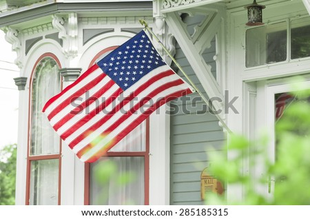 An American home proudly displaying their flag. - stock photo