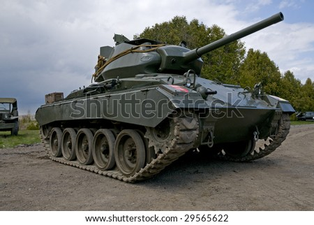 An American made M24 Chaffee light tank, circa 1944, flanked by US military vehicles of the same vintage. Storm clouds are moving in from the left. - stock photo