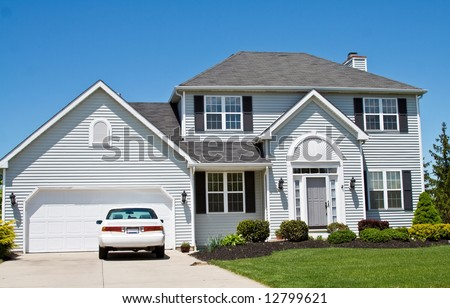 An American Ohio suburban home - neat and tidy.  One car in the driveway. - stock photo