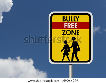 An American road warning sign with sky with children walking symbol and words Bully Free Zone, Caution This is a Bully Free Zone  - stock photo