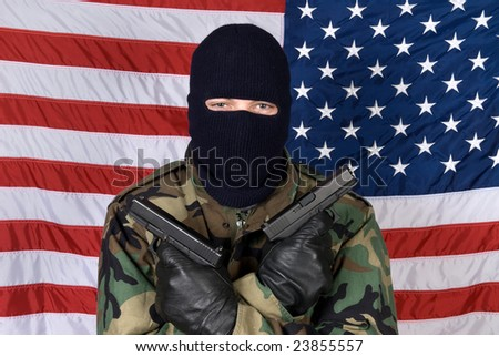An American stands prepared to protect his country from terrorism with his handguns. - stock photo
