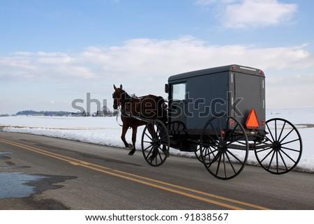 An Amish Carriage travels in snow covered Lancaster County,Pennsylvania,USA. - stock photo