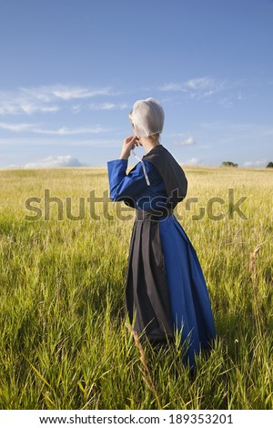 An Amish woman standing in a grassy field in afternoon sunlight - stock photo