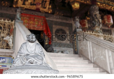 An ancient buddha statue at the steps to an exotic old Chinese temple in Georgetown city, Penang, Malaysia. - stock photo