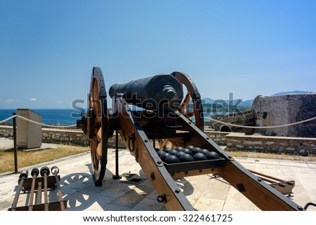 An ancient cannon with shots at the wall of Corfu Old Fortress, Greece. - stock photo