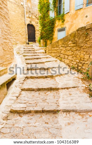 An ancient cobblestone footpath winds its way around the picturesque medievel village of Gordes in Provence, France - stock photo