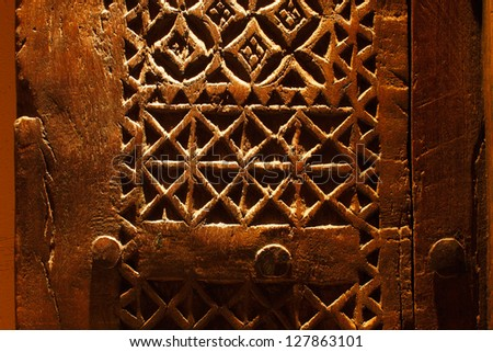 An ancient hand carved door from Arabia, the design is wonderfully interact and it's irregularity exemplifies that it was definitely hand carved - stock photo