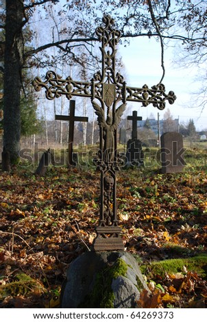 An ancient iron cross in old graveyard - stock photo