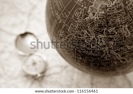 An ancient map of the world with a compass on the backgorund - stock photo