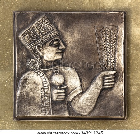 An ancient Mayan relief on bronze tablet with golden tones. - stock photo