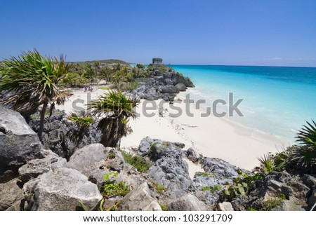 An ancient Mayan ruin overlooking the teal blue waters of the Mexican Riviera beach. Sandy cove with Palm trees. Tourists walking in the distance. Focus is mainly on the foreground rocks and beach. - stock photo
