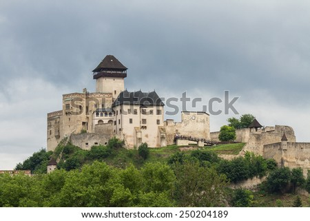 An ancient medieval castle on the hill light among green trees in the city of Trencin in Slovakia