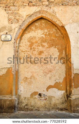 """An ancient, run-down brick and stone wall in Italy with a filled-in archway and a sign reading """"Via dei Tabacchi"""" (Tobacco Road).  Symbolizing that tobacco leads you nowhere, except to ruin. - stock photo"""