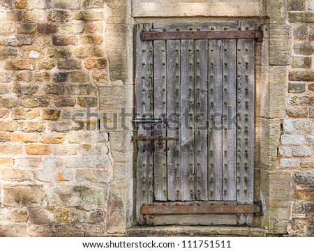 An Ancient Wooden Door in an Old Brick Wall