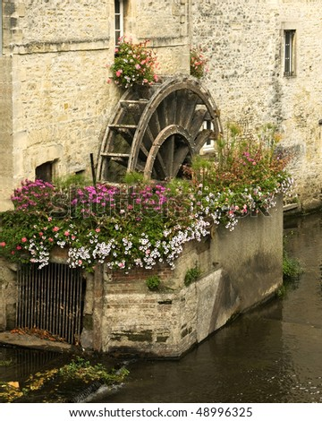 An ancient wooden mill wheel and small canal in the old part of Bayeux, France.  The area around the wheel is decorated with flowers, and the old stone buildings  have interesting textures. - stock photo