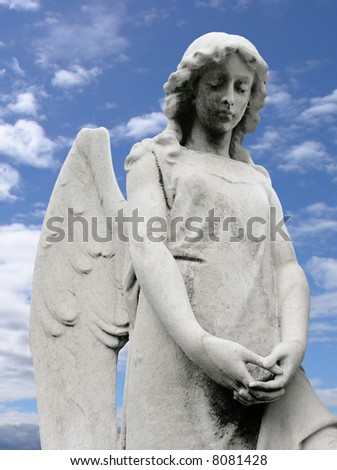 An angel scuplture with a blue sky background. - stock photo